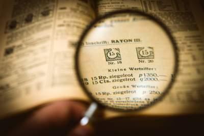 Philatelist recherchiert mit Lupe in einem Briefmarkenkatalog